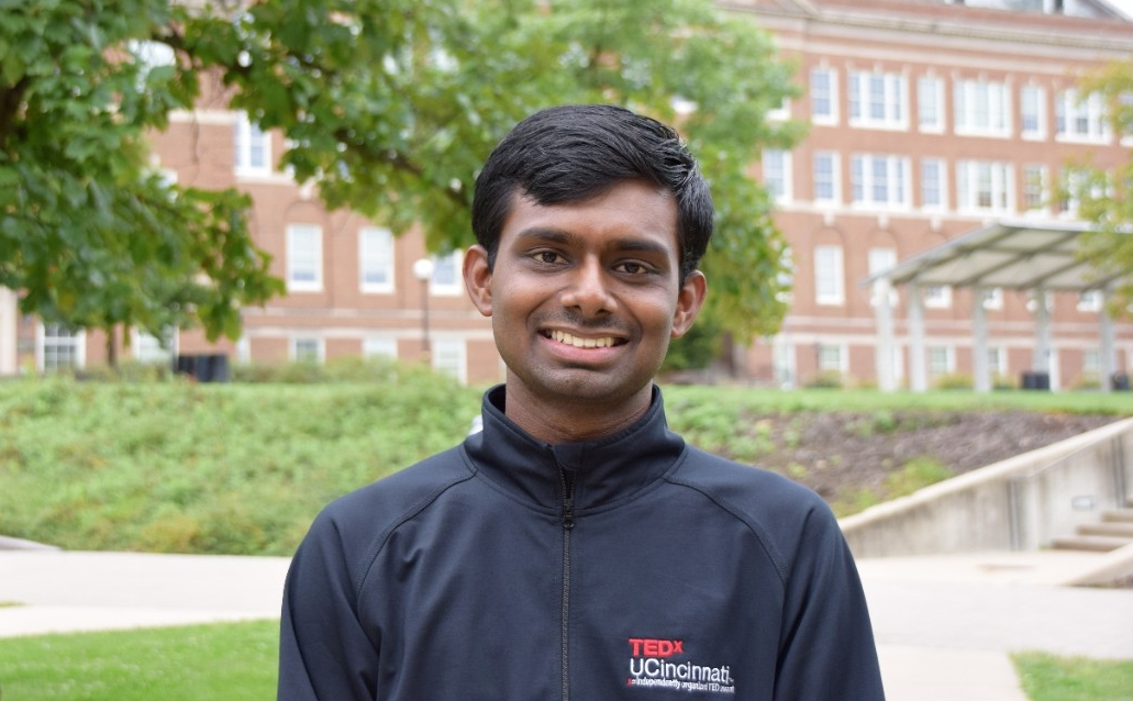 Casual portrait photo of a smiling graduate student, with a red brick building in the background.