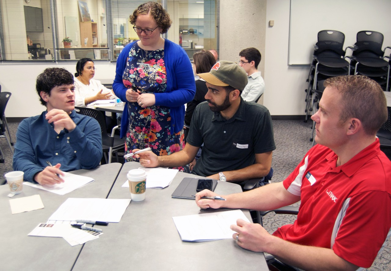 Graduate students sit at a round table and talk at a workshop.