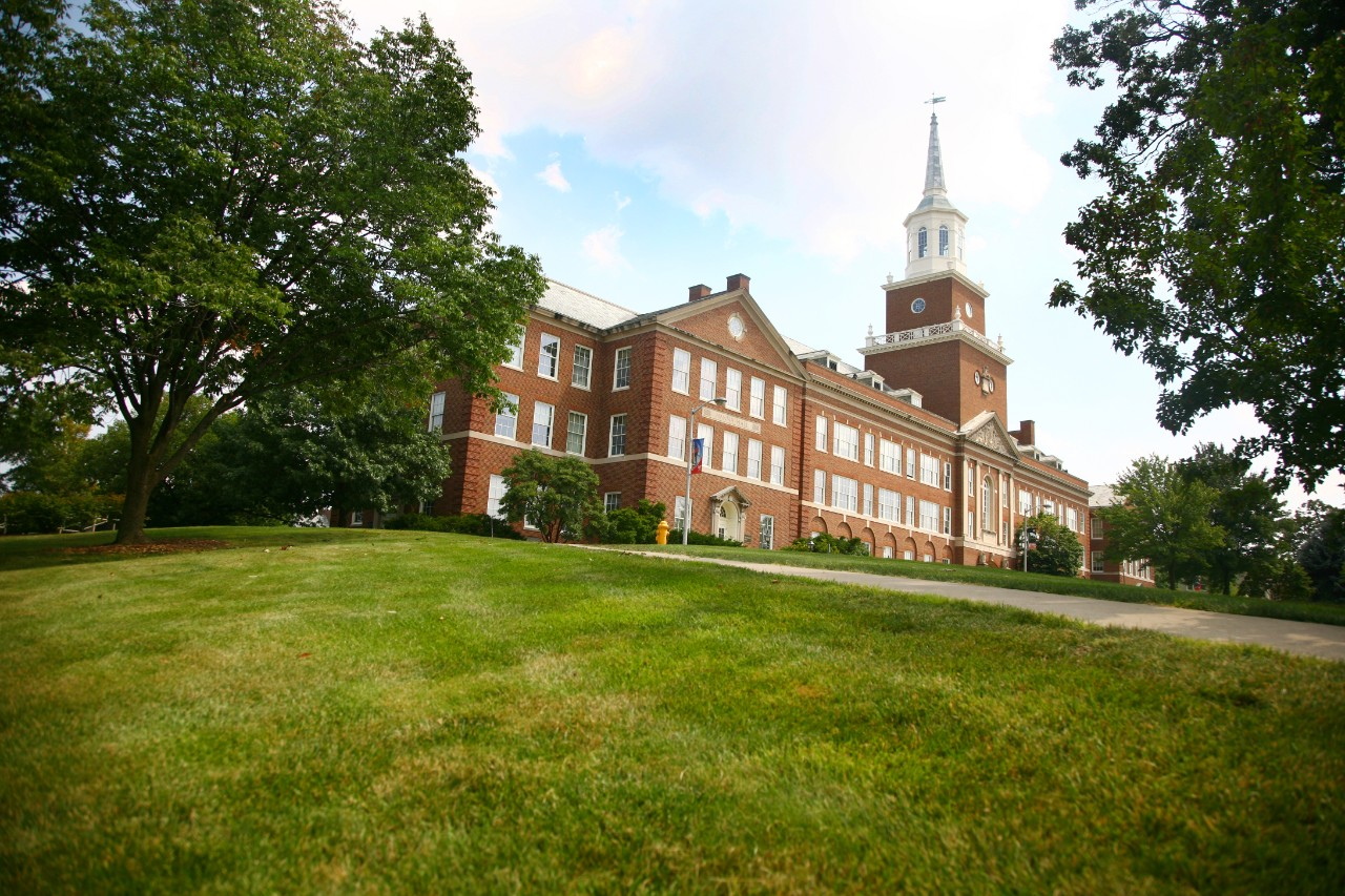A view of McMicken Hall at the top of a green hill.
