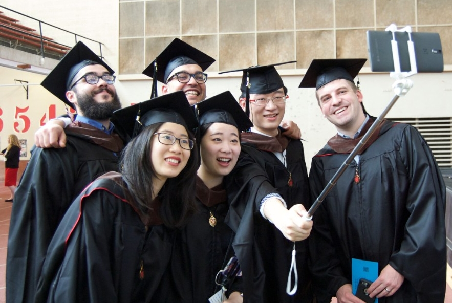 Master's students taking a group selfie at graduation.