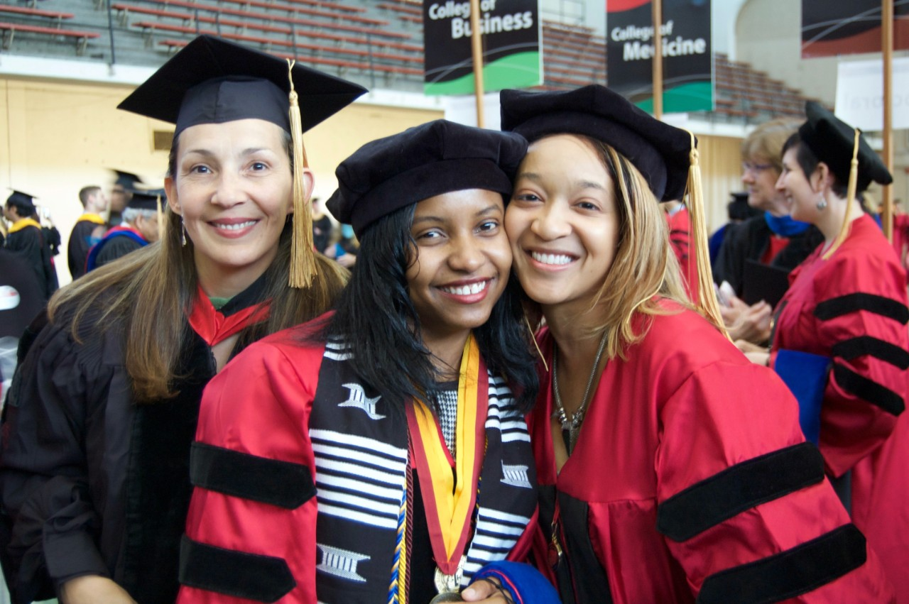 Two graduating doctoral students pose with their advisor at the hooding ceremony.