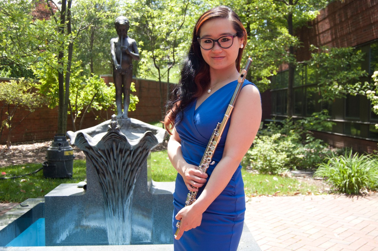 A graduate student poses with her flute in front of a fountain on campus.