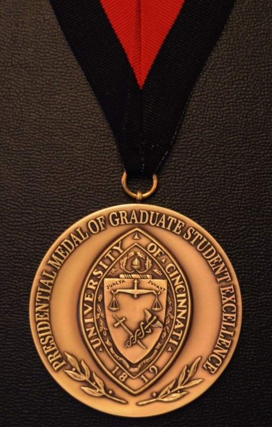 A medal with the university seal hanging on a black and red ribbon.