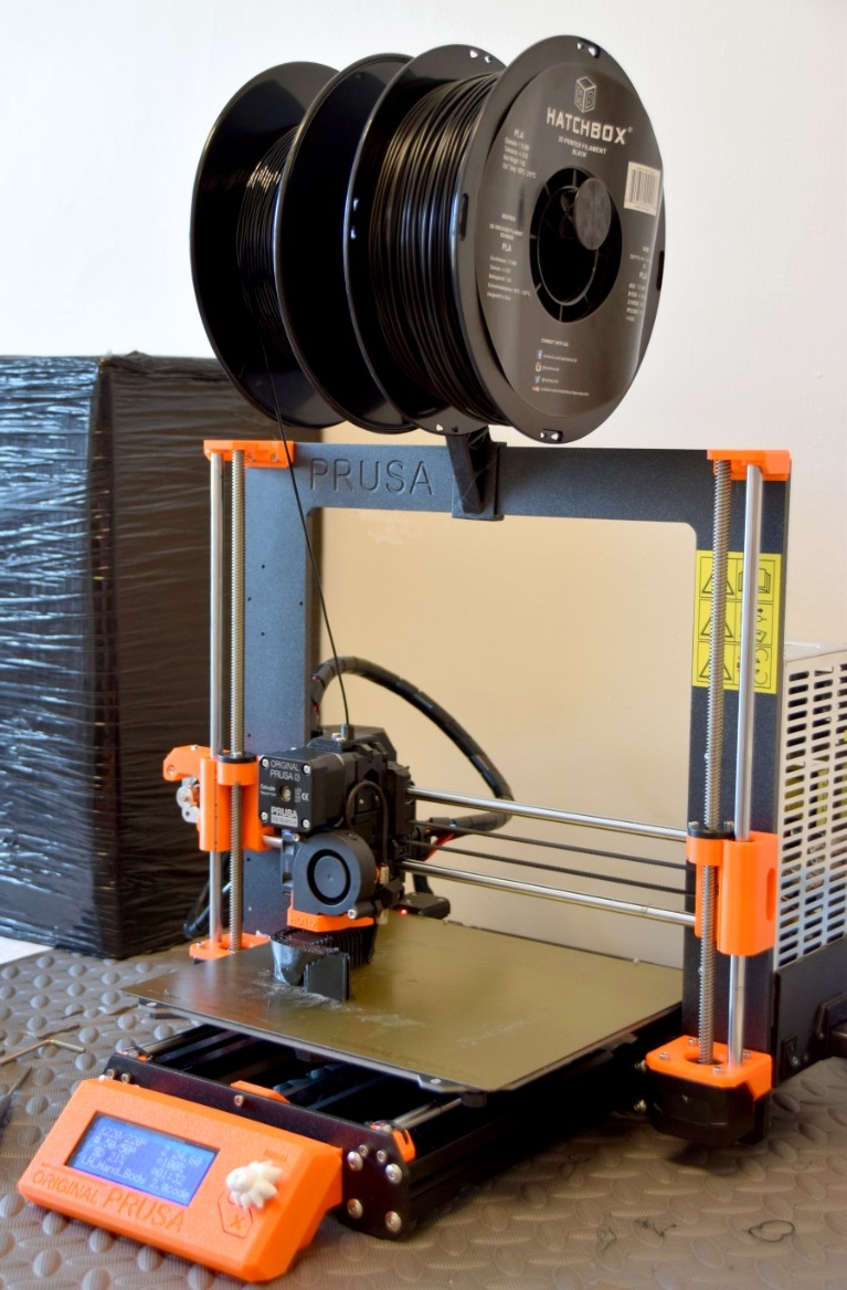 A desktop-sized 3D printer with a spool of black  plastic rope.