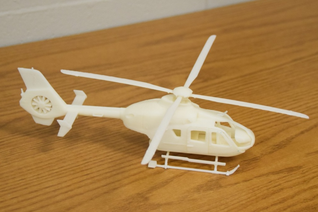 A small, cream-colored model of a helicopter with fine detailing, created with 3-D printing.