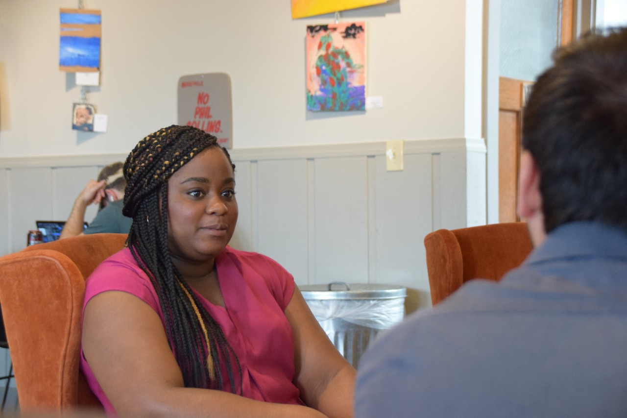 Rashida speaking with a student about her work at Green Umbrella.